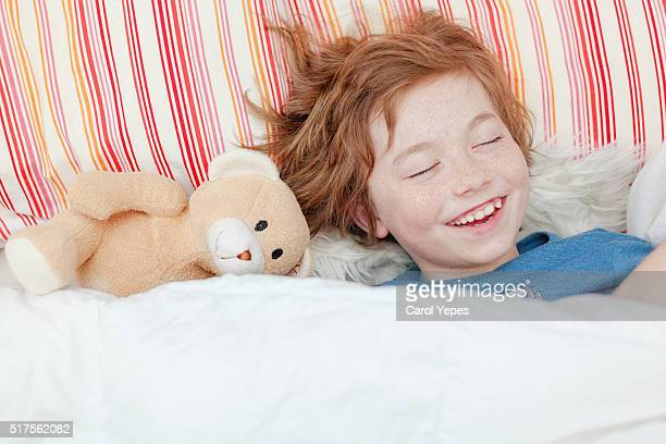 stuffed animal teddy bear peeks out from covers where child is hiding