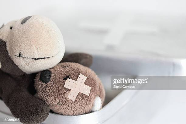 Stuffed animal with bandage on stomach