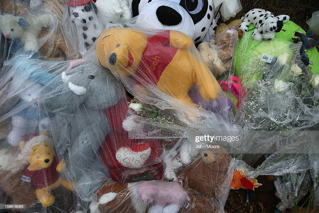 Stuffed animals lie covered to protect them from the rain at a streetside memorial on December 21, 2012 in Newtown, Connecticut. Church bells rang out at 9:30 EST to mark the one-week anniversary of the Sandy Hook Elementary School massacre.