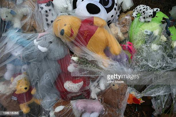 Stuffed animals lie covered to protect them from the rain at a streetside memorial on December 21 2012 in Newtown Connecticut Church bells rang out...