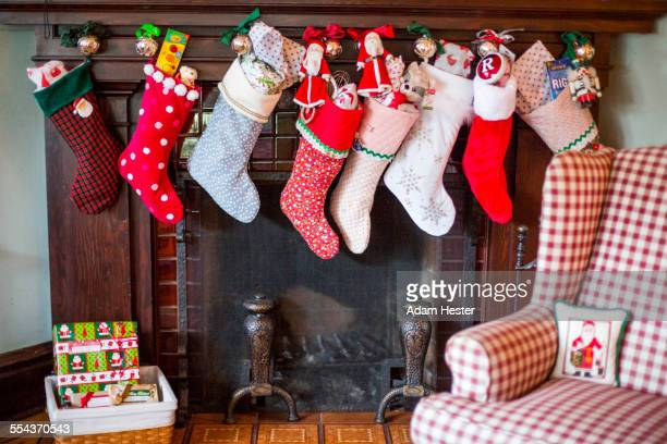 Stuffed Christmas stockings over fireplace
