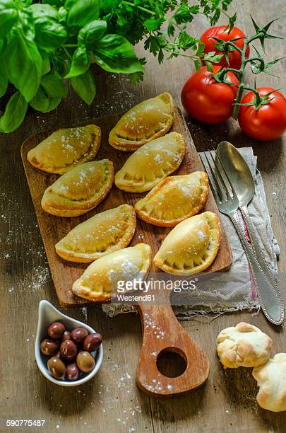 stuffed pastry with black olives, tomatoes and basil on wooden board - flat leaf parsley stock pictures, royalty-free photos & images