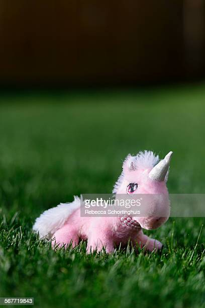 Stuffed pink unicorn toy on green grass