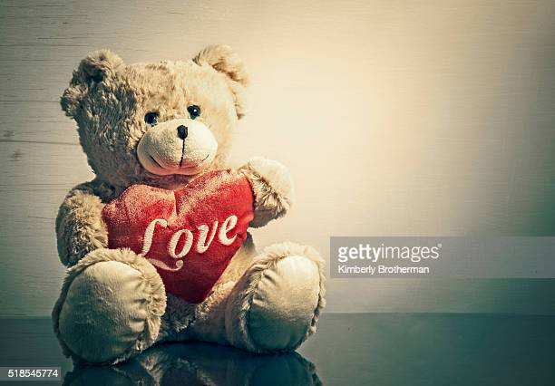 stuffed teddy bear holding a red heart - teddy bear stock photos and pictures