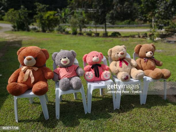 stuffed teddy bears on chairs in lawn - toy animal stock photos and pictures