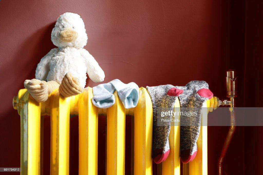 stuffed toy and socks on radiator : Stock Photo