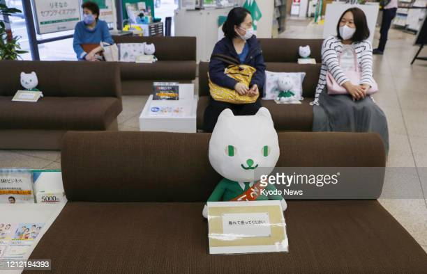 Stuffed toy featuring Resona Bank's cat mascot is left at the center of each couch at a Tokyo branch of the bank on May 8 so that customers do not...