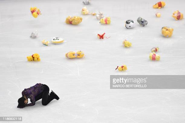 Stuffed toys thrown by fans scatter the ice rink as Japan's Yuzuru Hanyu reacts after performing during the Men Free Skating program on December 7,...