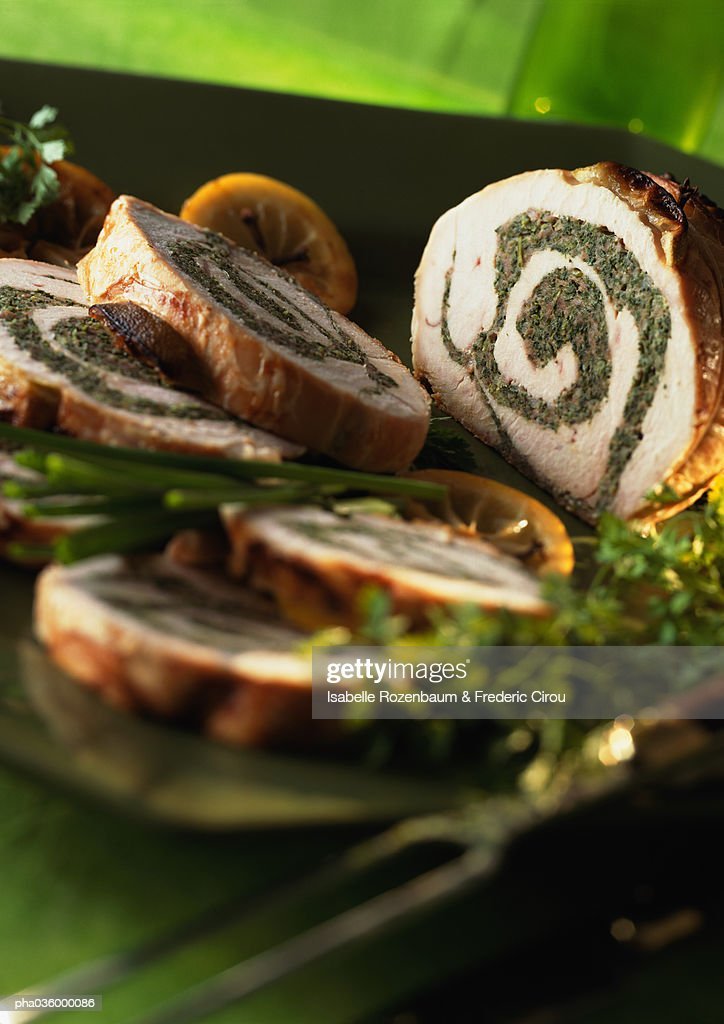 Stuffed turkey roll cut into slices, garnished with herbs and lemon slices, close-up : Stockfoto
