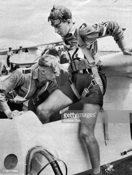 Stuka Pilot is helped to climb into his cockpit Swastika worn on his shirt sleeve Wiener Illustrierte 2 September 1942 Caption reads 'Fertig zum...