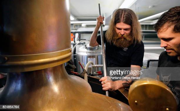 Stulli Bjornsson left and Greg Abbot mix malt into mash on Thursday at Liquid Riot on Commercial Street for a smallbatch beer Bjornsson is brew...