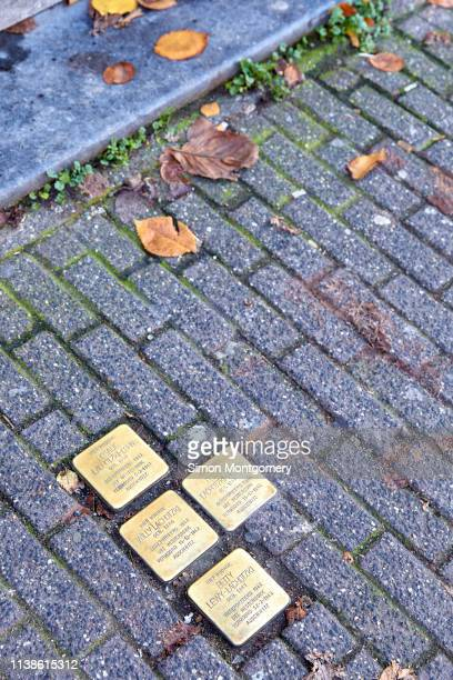 stumbling stones or stolpersteine are holocaust memorial brass plaques placed in front of the victims last home, kloveniersburgwal in amsterdam - last stock pictures, royalty-free photos & images