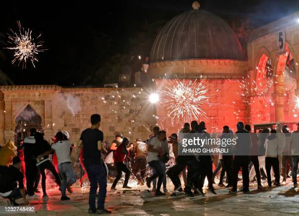 Stun grenades burst in the air amid clashes between Palestinian protesters and Israeli security forces at the al-Aqsa mosque compound in Jerusalem,...