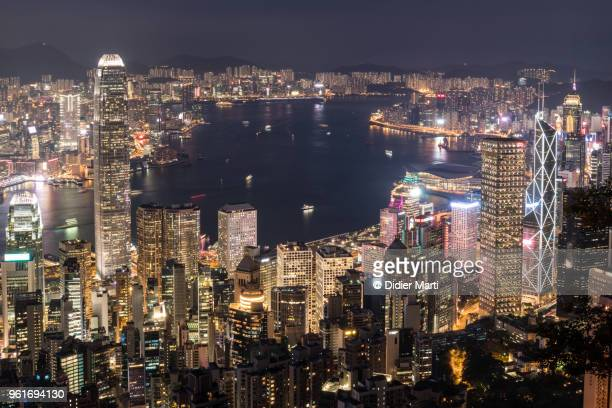 Stunning aerial view of Hong Kong island financial district and Kowloon across the Victoria harbour from Victoria peak at night in Hong Kong