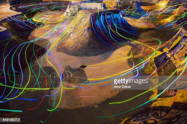 Stunning colorful long exposure view with light trails flowing with nice visual motion at night in a urban skatepark in the city.