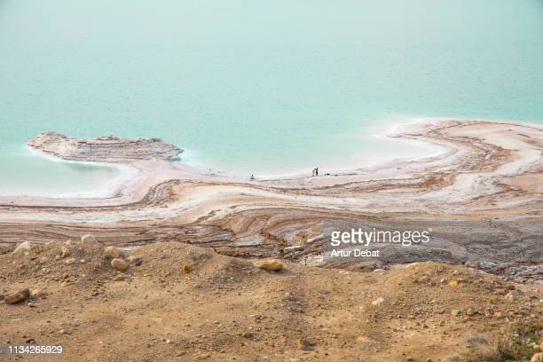 stunning colors of the dead sea with tiny people. - 死海 ストックフォトと画像