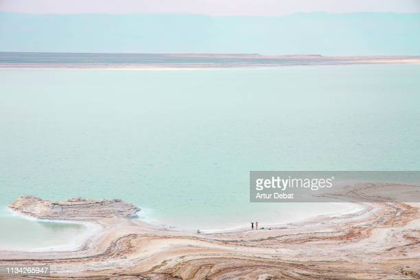 stunning colors of the dead sea with tiny people. - dead sea stock pictures, royalty-free photos & images