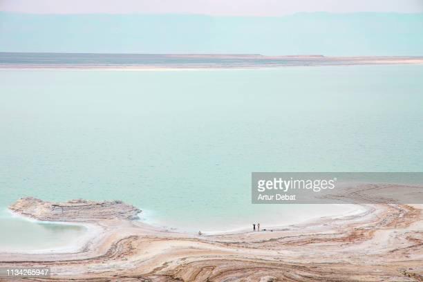 stunning colors of the dead sea with tiny people. - mar muerto fotografías e imágenes de stock