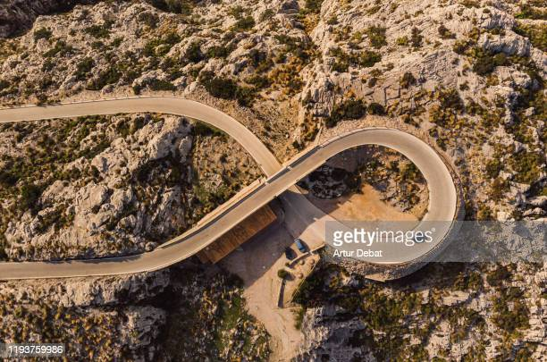 stunning drone view of helicoid curve with eight shape with tunnel in winding road in the mountains of mallorca island. - lugar famoso internacional fotografías e imágenes de stock