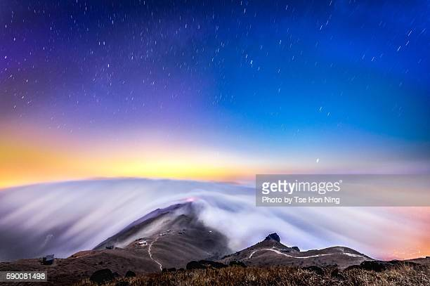 Stunning flowing clouds on the mountain below starry night sky