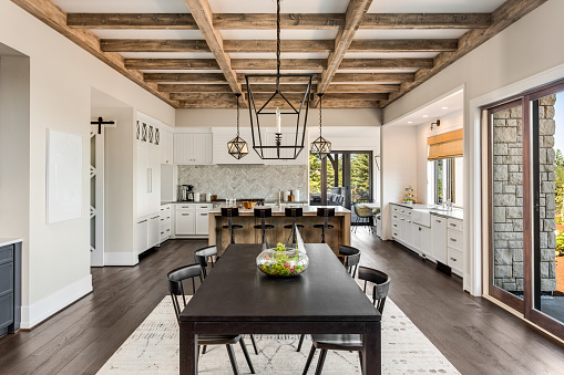 Stunning kitchen and dining room in new luxury home. Wood beams and elegant pendant lights accent this beautiful open-plan dining room and kitchen 950127464