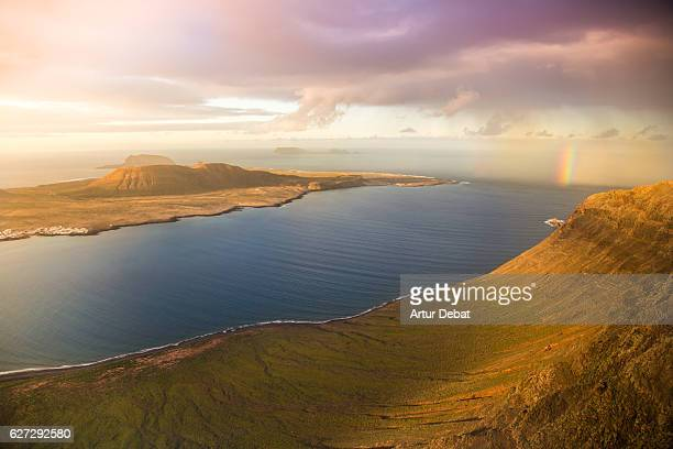 Stunning landscape view from top of viewpoint in the volcanic island of Lanzarote with beautiful cliffs, islands and nice rainbow during the sunset light of the day.