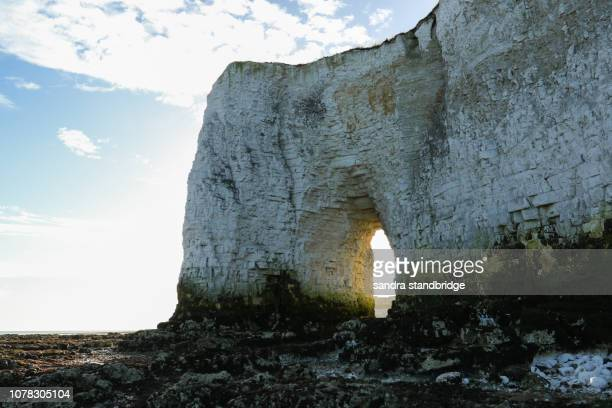 a stunning landscape view of a coastal bay at kingsgate, thanet, kent, uk. kingsgate castle can be seen through the arch in the chalk cliffs. - hertford hertfordshire stockfoto's en -beelden