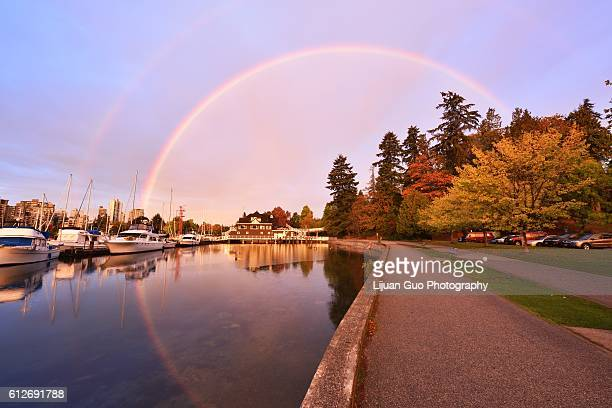 stunning morning rainbow over yacht club in stanley park, vancouver - stanley park stock photos and pictures