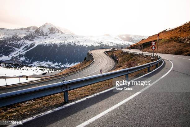 stunning mountain road pass in the pyrenees with curve and snowy summits. - andorra stock pictures, royalty-free photos & images
