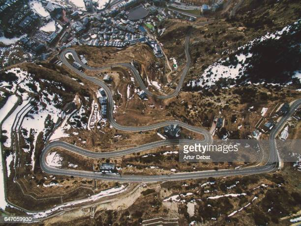 Stunning mountain road with nice curves between the mountains with snow landscape during winter in the Andorra Pyrenees mountains.