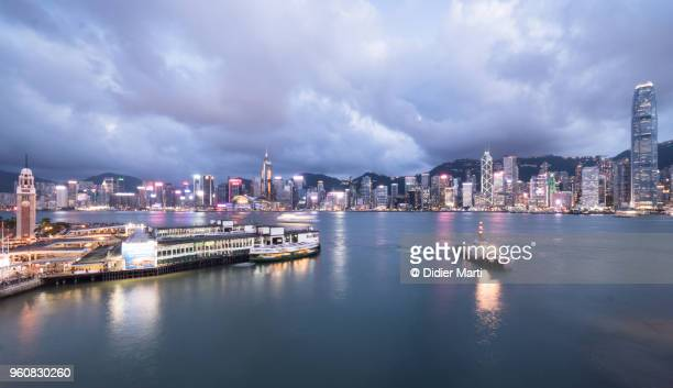 Stunning panorama at dusk of the famous Victoria Harbor in Hong Kong with the financial district skyline of Hong Kong island