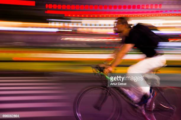 Stunning picture of cyclist in motion in the streets of Shibuya with colorful background taken during travel vacations in Tokyo.