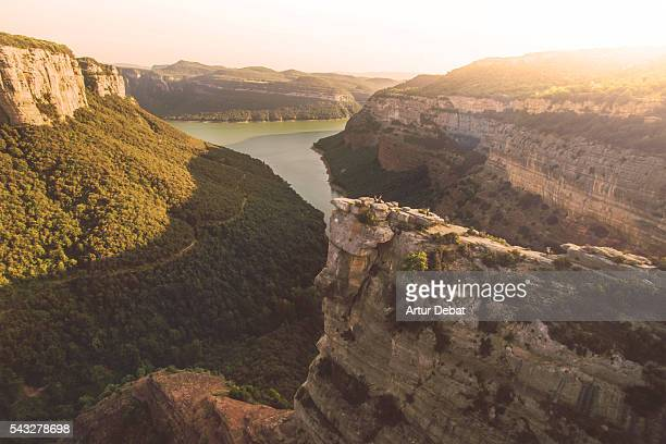 Stunning rock pulpit formation taken from elevated viewpoint with the landscape and lake with vertical rock formations on sunset in the Catalonia region.