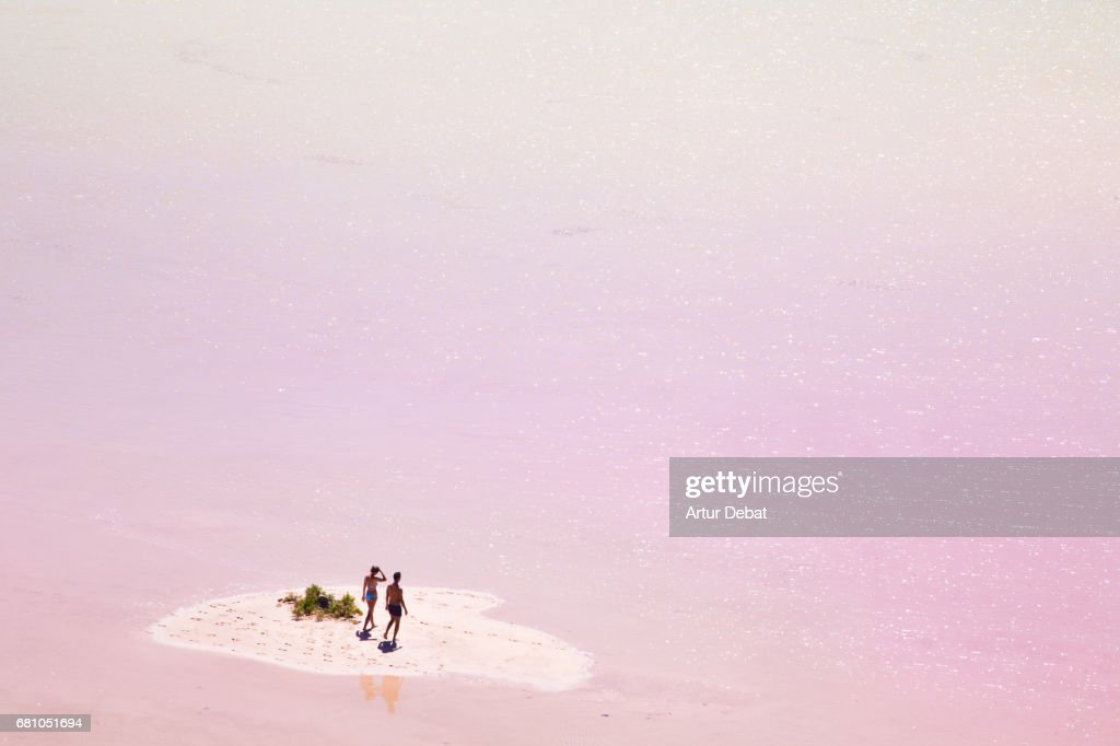 Stunning small island in the middle of the pink lagoon with couple enjoying the beach day in the Fuerteventura island during travel vacations. : Stock Photo