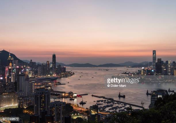 Stunning sunset over the Hong Kong island skyline and Kowloon separated by the famous Victoria harbour in Hong Kong