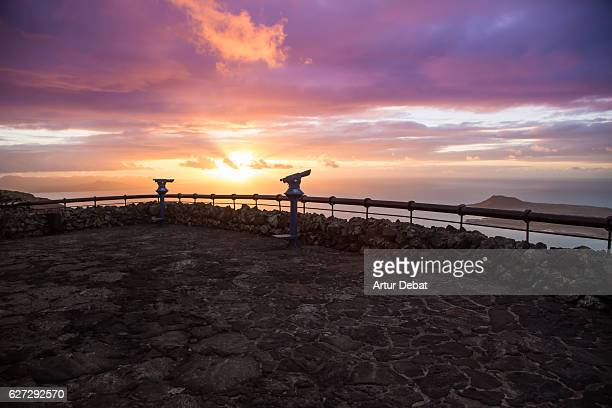 Stunning sunset sky over the volcanic island of Lanzarote taken from elevated viewpoint over the cliffs and islands during a travel vacations.