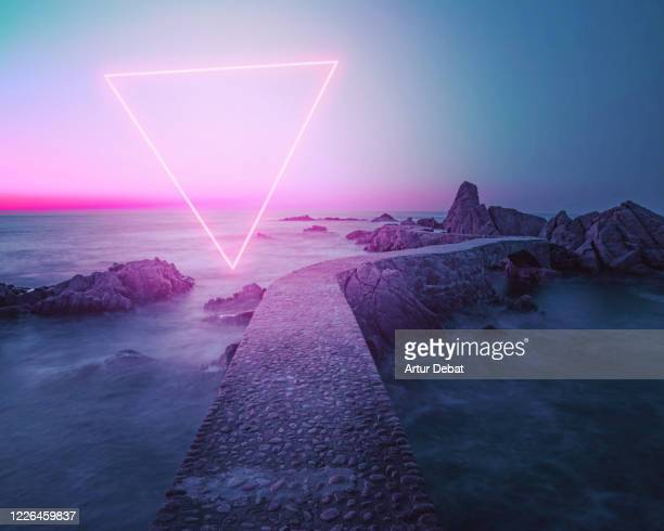 Stunning triangle shape made with neon light performing in the coast with path between rocks during sunrise.