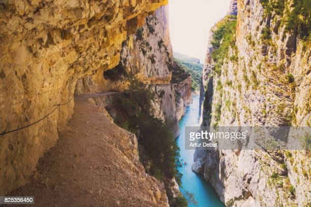 stunning view from footpath in the rock on top of the edge with cliff and stunning views of the river in the congost de montrebei with mountains in the catalan pyrenees. - formazione rocciosa foto e immagini stock