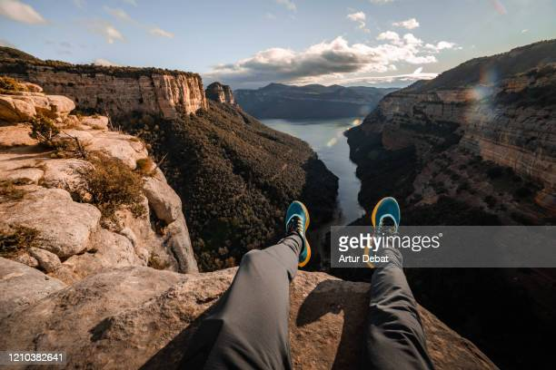stunning view from personal perspective in rocky mountains sitting on the edge. - cena de tranquilidade imagens e fotografias de stock