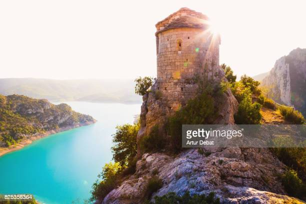 Stunning view of a ancient chapel on top of the edge with cliff and stunning views of the lake and mountains in the Catalan Pyrenees mountains.