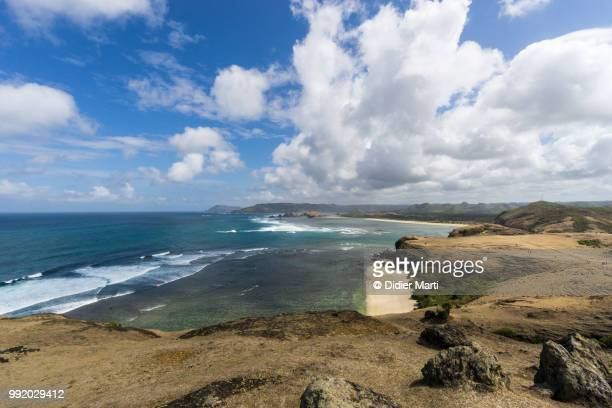 stunning view of the south lombok coast toward kuta from the marese hill by the tanjung aan bay in lombok in indonesia - didier marti stock photos and pictures