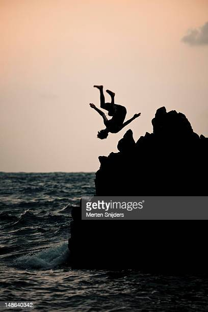 stunt diving from cliff at red sand beach. - merten snijders 個照片及圖片檔