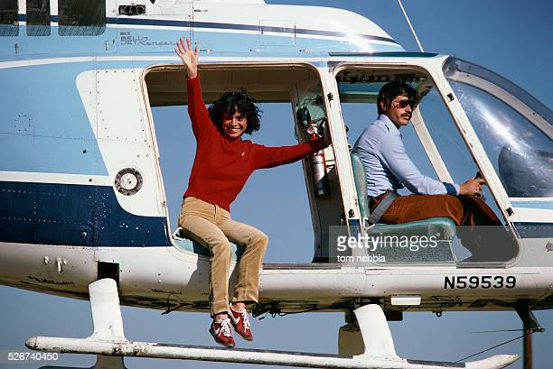 A stunt performer playing Lynda Carter in Wonder Woman waves from a helicopter before jumping