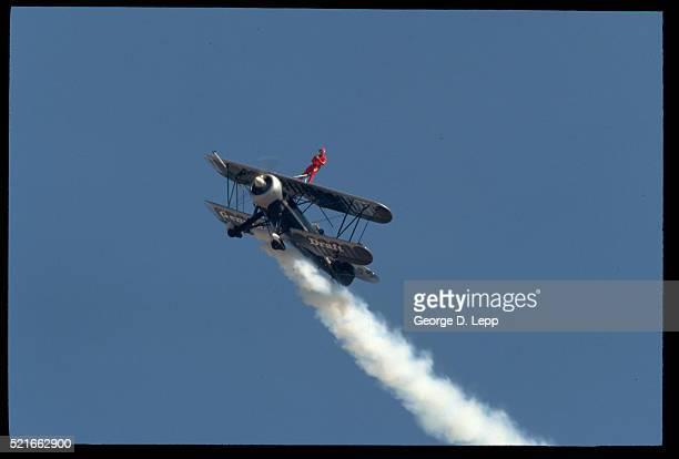 stunt performer wing walking - doppeldecker flugzeug stock-fotos und bilder