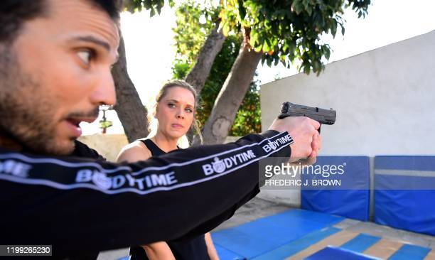 Stuntman Daniel Locicero demonstrates proper grip and technique of using a weapon for actress Courtney M Moore during a training session in Los...