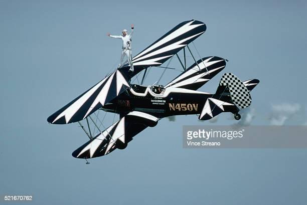 stuntman standing on wing of biplane - doppeldecker flugzeug stock-fotos und bilder