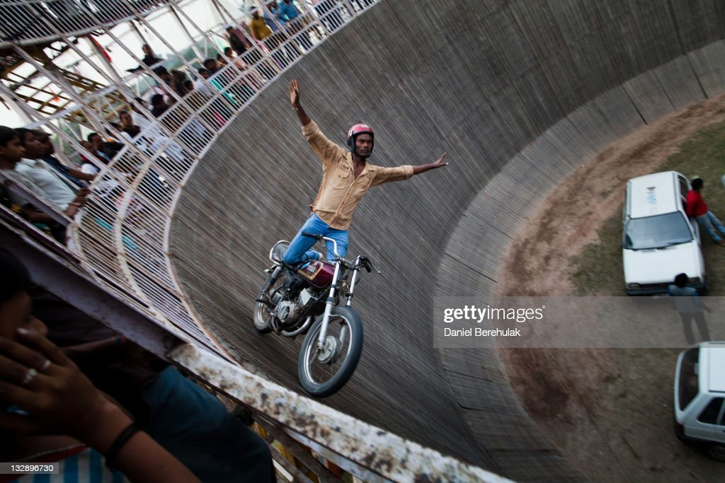 A stuntman stands on a motorbike as he performs on the inside of an attraction called the 'Well of Death' during the Sonepur Mela on November 15, 2011 in Sonepur near Patna, India. The cattle fair, held in the Indian state of Bihar, has its origins during ancient times, when people traded elephants and horses across the auspicious river Ganges. The mela used to attract traders from places as distant as Central Asia. It is one of Asia's largest cattle fairs and lasts for a fortnight.