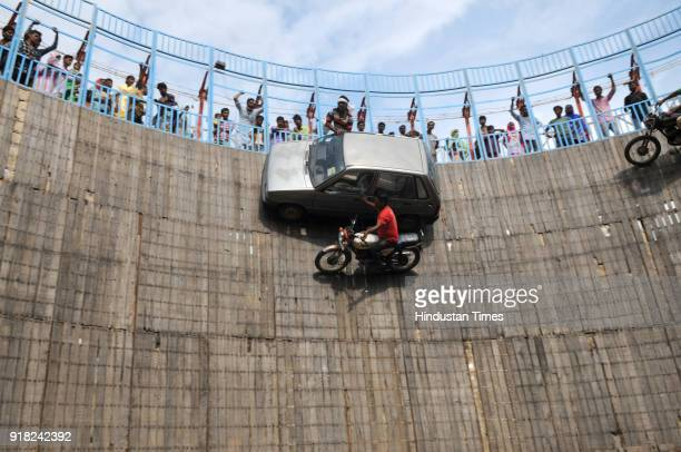 Stuntmen Mustakeem 30 Saleem 27 and Aarif 28 drive their bikes and hang out of the window of cars as they steer them in front of the crowd at an...