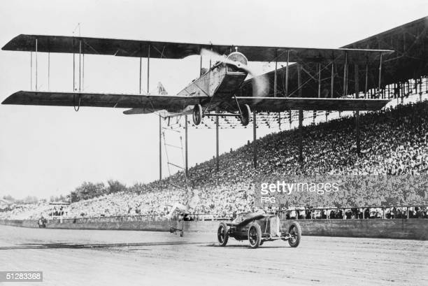 A stuntperson leaps from a moving car onto a ladder dangling from a biplane in flight circa 1920