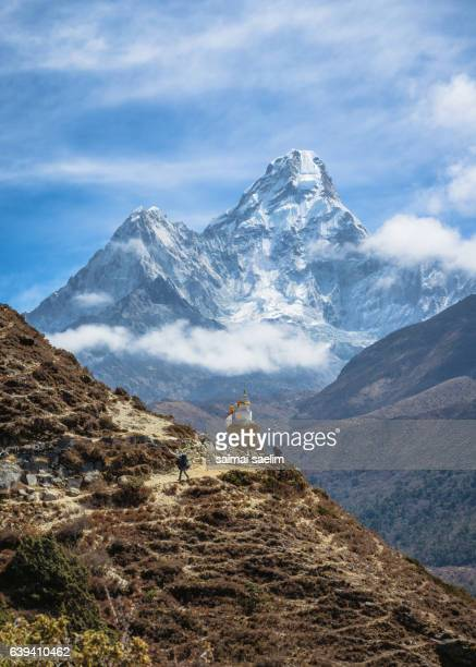 Stupa and Sherpa Porter in front of Ama Dablam mountain peak